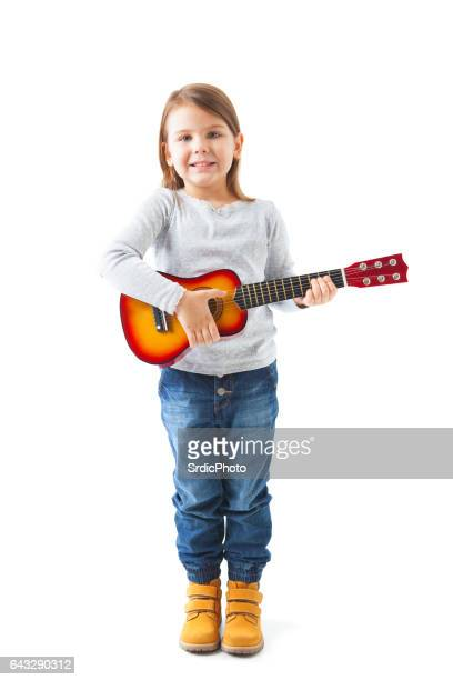 Happy little girl posing with acoustic guitar