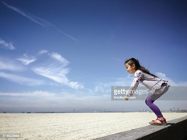 Happy little girl readies herself to jump on sand