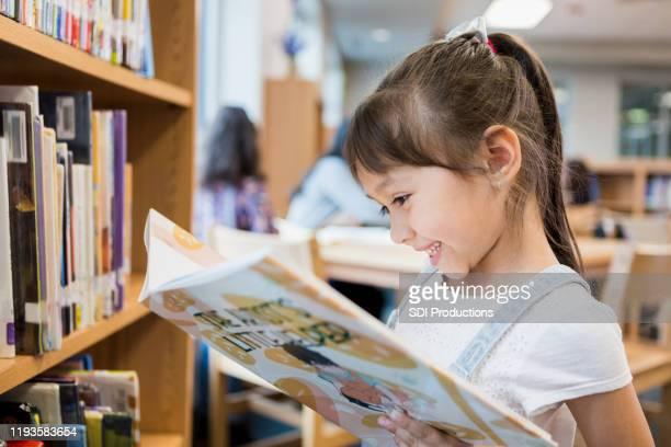 la bambina felice legge il libro nella biblioteca della scuola - legge foto e immagini stock