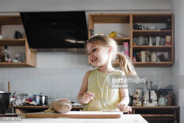 happy little girl rolling out dough in the kitchen - 4 5 anni foto e immagini stock