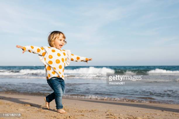 happy little girl running barefoot on the beach - toddler stock pictures, royalty-free photos & images