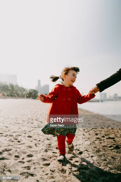 Happy little girl running on beach in winter, Tokyo
