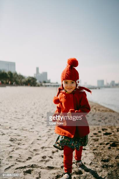 Happy little girl running towards camera on beach in winter, Tokyo
