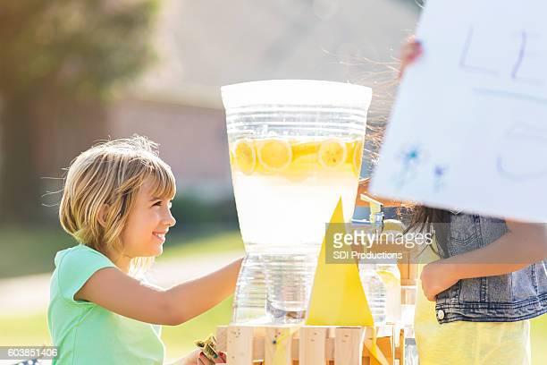 Happy little girl sells lemonade in front yard