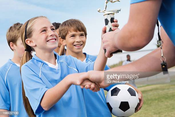 Happy little girl shaking hands with soccer coach receiving trophy