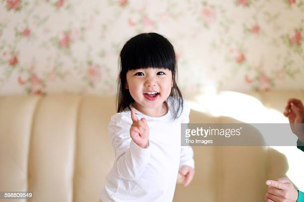 happy little girl singing on bed