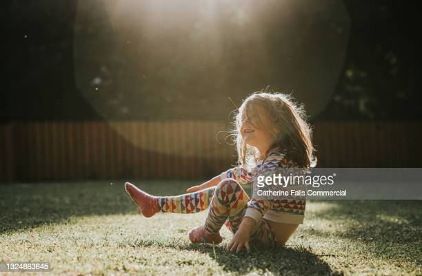 a happy little girl sits on the grass in her pyjamas in a sunny garden - sunbeam stock pictures, royalty-free photos & images