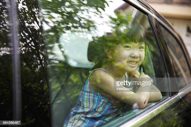 Happy little girl sitting in the car