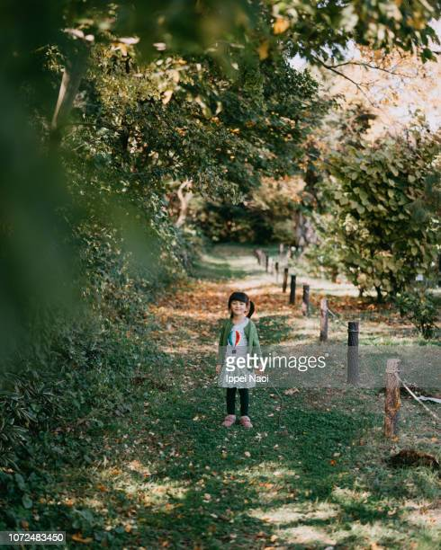 Happy little girl standing under tree canopy and smiling at camera, Tokyo