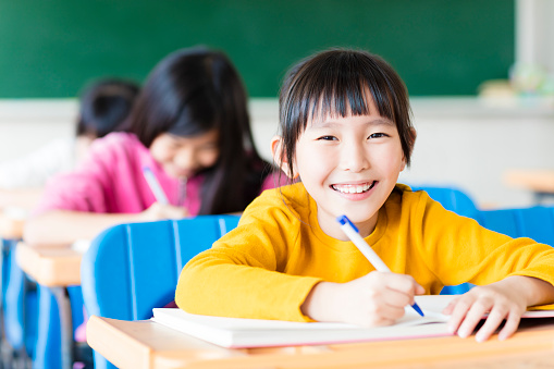 happy little girl student studying in the classroom 647497858