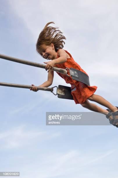 Happy Little Girl Swinging on Swing