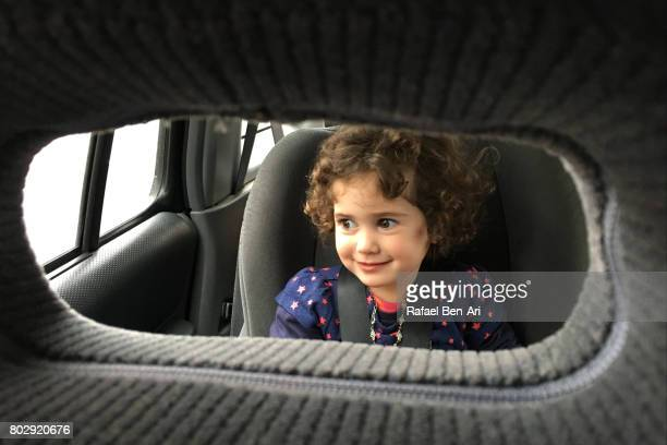 happy little girl travels in a booster car seat - rafael ben ari stock pictures, royalty-free photos & images