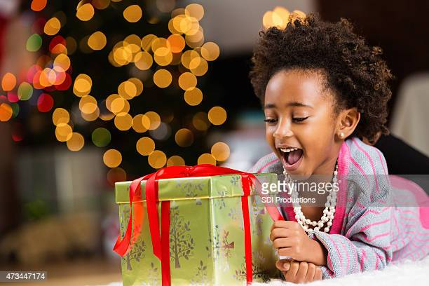Happy little girl unwrapping Christmas present at home