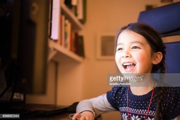 Happy little girl using a computer at home