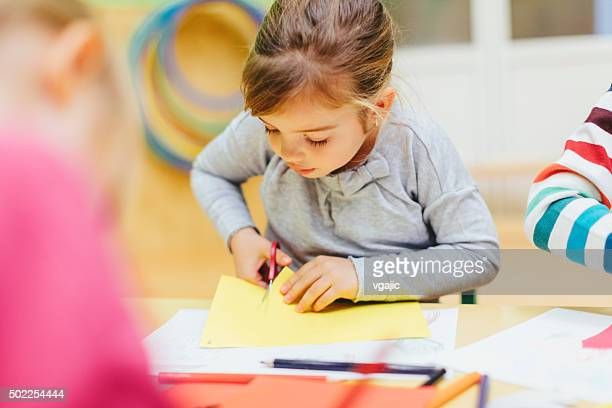 happy little girl using scissors. - preschool building stock pictures, royalty-free photos & images