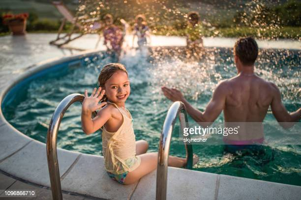 happy little girl waving at the poolside. - waving gesture stock pictures, royalty-free photos & images