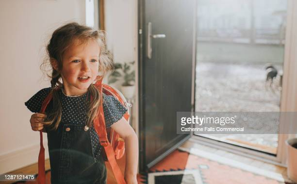 happy little girl wears a backpack in a sunny environment - childhood stock pictures, royalty-free photos & images