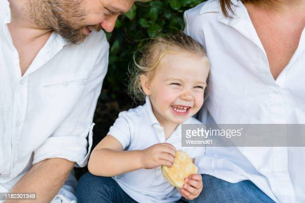 happy little girl with a snack sitting amidst parents - femme entre deux hommes photos et images de collection
