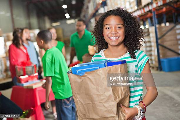 Happy little girl with bag of donations at food bank