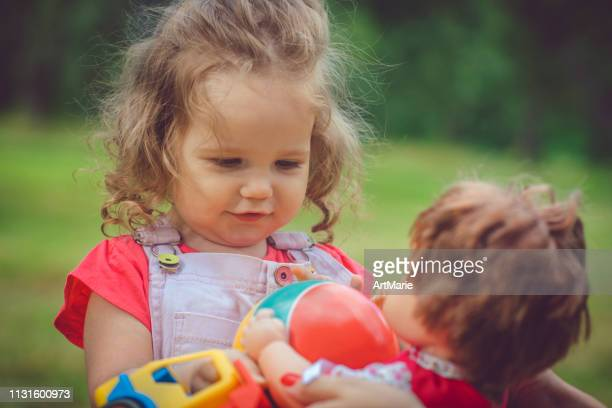 happy little girl with ball in summer outdoors - doll stock pictures, royalty-free photos & images