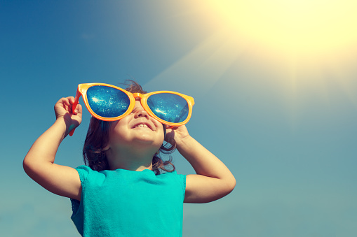 Happy little girl with big sunglasses looking at the sun 543562666