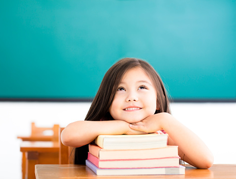 happy little girl with books and thinking in classroom 666805782