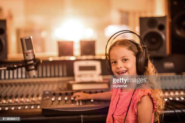 レコーディング スタジオでヘッドフォンで幸せな小さな女の子。 - ラジオdj ストックフォトと画像