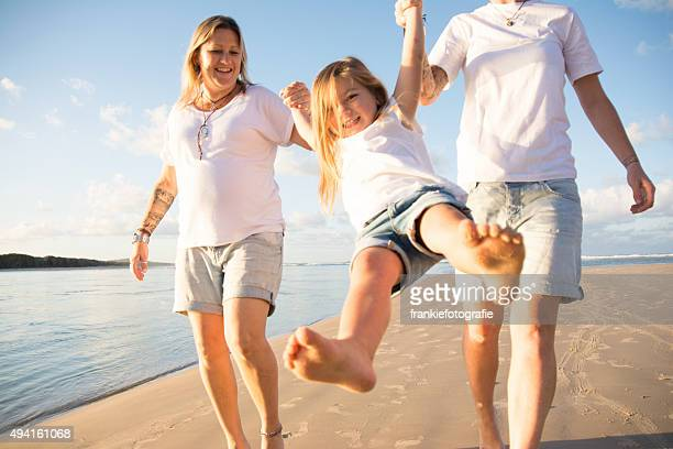 happy little girl with her two mum's - community engagement stock pictures, royalty-free photos & images