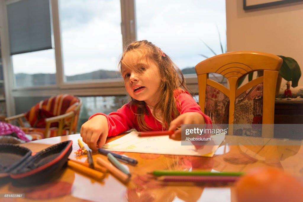 Glückliches kleines Mädchen mit langen Haaren Zeichnung im Zimmer : Stock-Foto