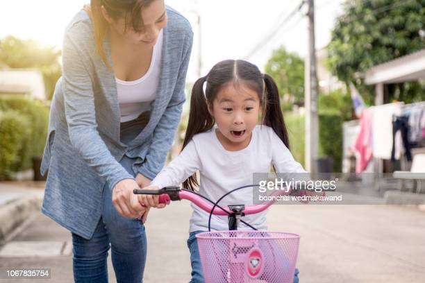 happy little girl with mother practice to riding bicycle - very young thai girls stock photos and pictures