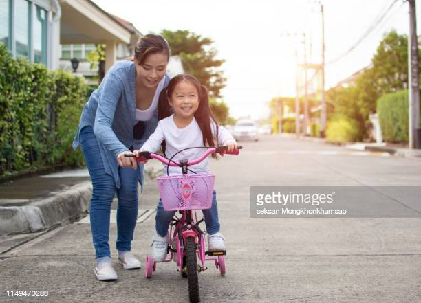 happy little girl with mother practice to riding bicycle - riding stock pictures, royalty-free photos & images