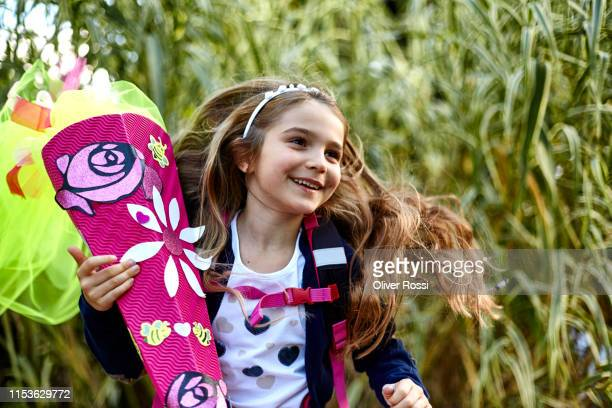 happy little girl with school cone in a field - der erste schultag stock-fotos und bilder