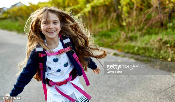 happy little girl with schoolbag on a country road - 6 7 jahre stock-fotos und bilder