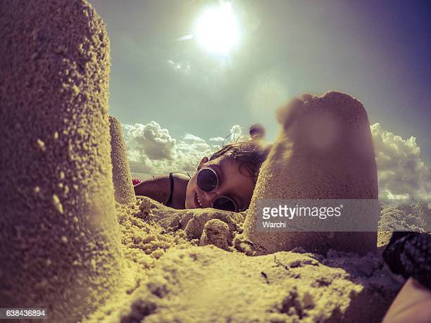 Happy little girl with sunglasses playing with sand on beach