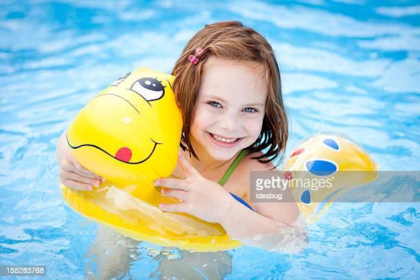 Glückliches kleines Mädchen mit Schwimmen, Sonnen und im Swimmingpool