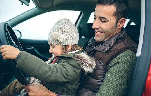 Happy little girl with wool cap driving car sitting on father's lap - gettyimageskorea