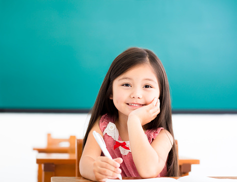 happy little girl writing at desk in classroom 666805404