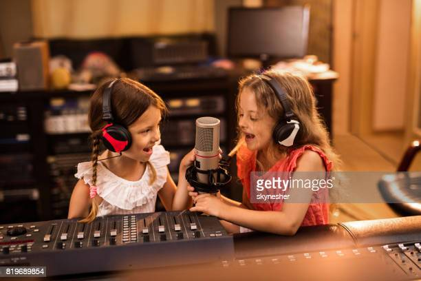 happy little girls broadcasting a radio show from the station. - sound recording equipment stock pictures, royalty-free photos & images