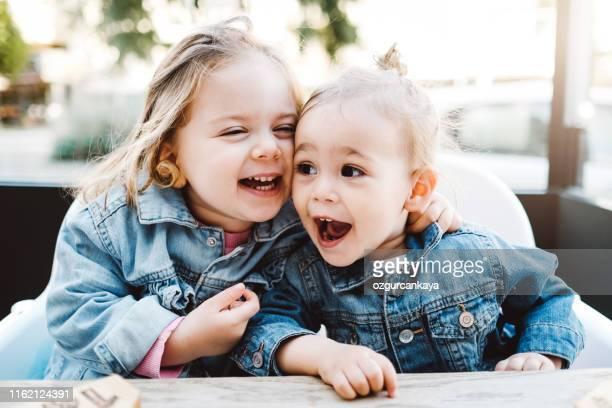 glückliche kleine mädchen genießen in waffel in einem café - schwester stock-fotos und bilder
