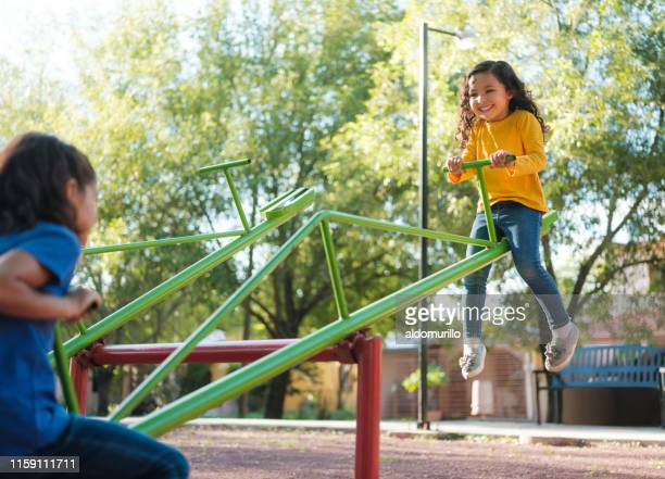 happy little girls on a teeter totter - seesaw stock pictures, royalty-free photos & images