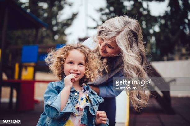 happy little grandmother and granddaughter having fun at the playground - granddaughter stock photos and pictures