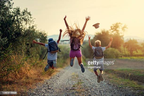 happy little hikers jumping with joy - criança imagens e fotografias de stock