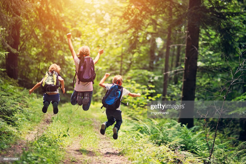 Happy little hikers jumping with joy : Stock Photo
