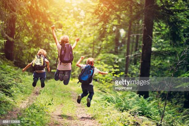 happy little hikers jumping with joy - woodland stock pictures, royalty-free photos & images