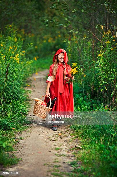Happy Little Red Riding Hood walking in forest