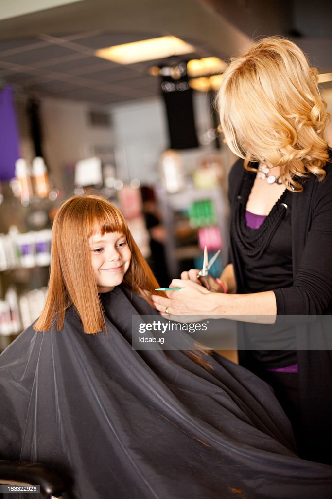 Happy Little Redhaired Girl Getting Haircut In Salon Stock Photo