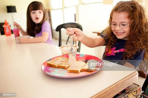 幸せな小さな姉妹一緒に自宅での朝食