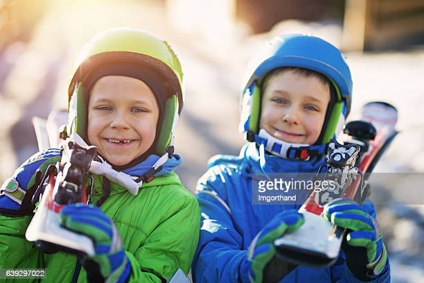 Happy little skiers carrying skis to the slope