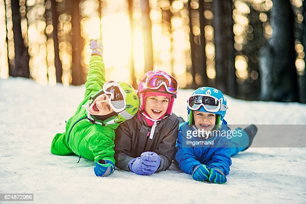 Happy little skiers lying on ski slope