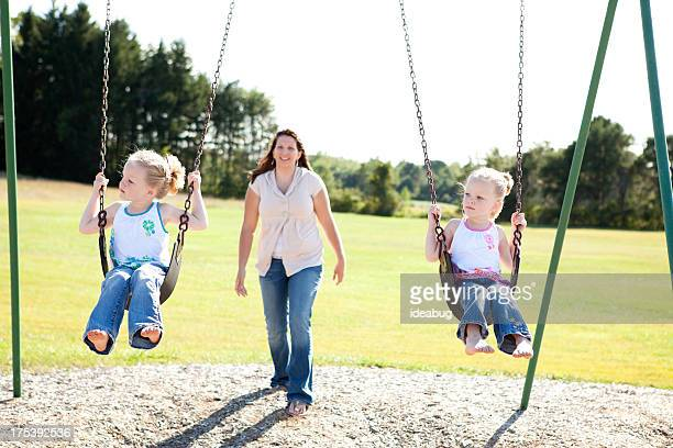 happy little twin girls swinging together outside on summer day - girls barefoot in jeans stock photos and pictures